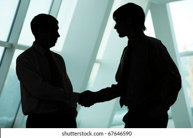 Silhouettes of two businessmen handshaking and greeting each other