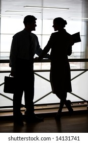 Silhouettes of two businesspeople standing on the balcony and looking at each other smiling