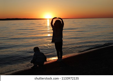 Silhouettes of two children looking on the sea against the sunset, beautiful summer evening, family vacation concept