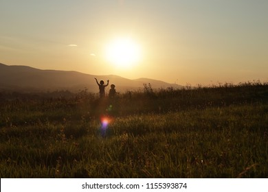 Silhouettes of two children looking on the setting sun in the mountains, beautiful summer evening, family vacation concept