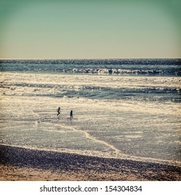Silhouettes of two children playing at ocean beach, vintage colors with vignette