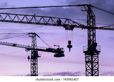 Silhouettes of two construction cranes