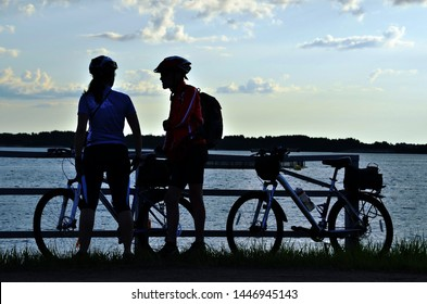 silhouettes of two cyclists on the countryside in the evening light