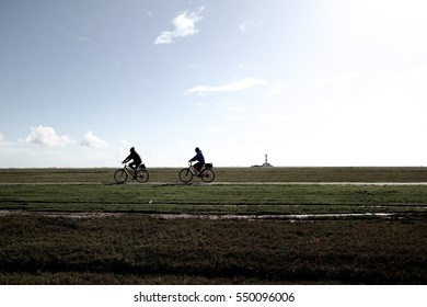 silhouettes of two cyclists in wide flat landscape with lighthouse in far distance