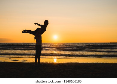 Silhouettes of two dancers doing acrobatics at sunset near the beach at the seaside