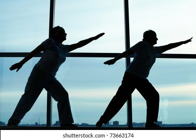 Silhouettes of two females doing physical exercise