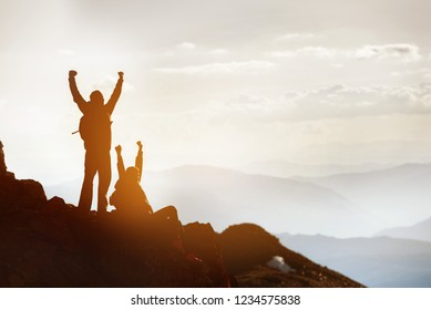 Silhouettes of two happy tourists at mountain top. Success or win concept