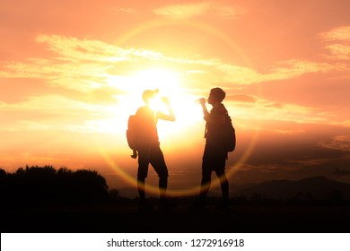 Silhouettes of two hikers with backpacks enjoying sunset. Travel concept