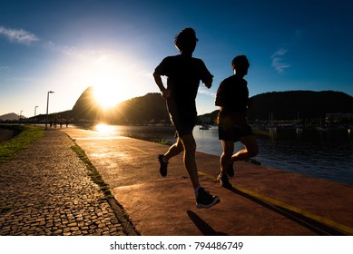 Silhouettes of Two Men Running in the Early Morning during Beautiful Warm Sunrise in Rio de Janeiro with Sugarloaf Mountain in the Horizon