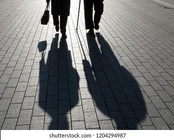 Silhouettes of two old people walking with cane and handbag on the street. Elderly couple outdoors, people shadows on pavement, concept for old age, social issues