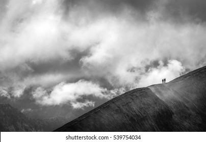 Silhouettes of two people hiking Mount Bromo - active volcano in Java, Indonesia