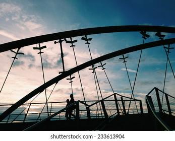 Silhouettes of two people walking on Frankston bridge in Melbourne, Australia