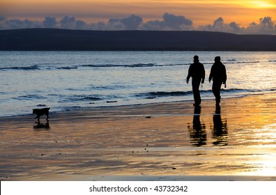 Silhouettes of two people walking with their dog on a beach at sunset.