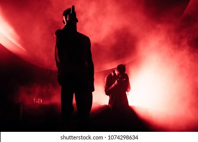 Silhouettes of two singers on the stage. Music band on the stage, red lightning. Rappers pulling out their hands on the stage.