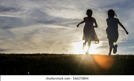 Silhouettes of two young children running towards the sunset over a hilltop