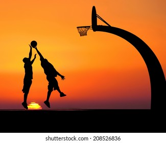 Silhouettes of two young men playing basketball in front of a dramatic sunset