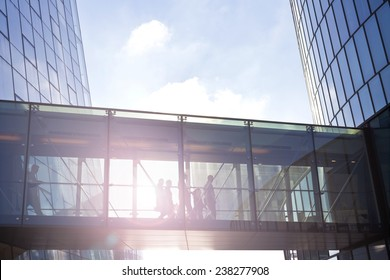 Silhouettes of unrecognizable business people using a transition between two contemporary office buildings.
