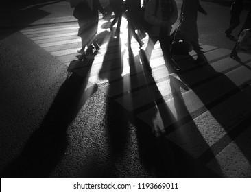 Silhouettes of walking people on crosswalk background