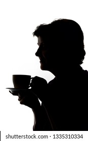 Silhouettes of woman drinking coffee in studio