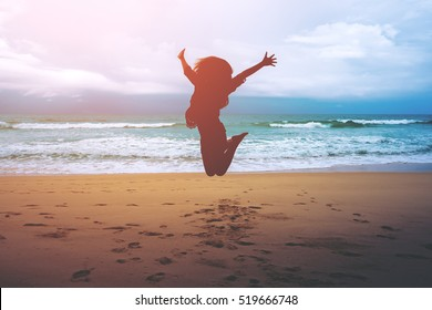 Silhouettes of a woman jumping on the beach in front of ocean with feeling happy and freedom