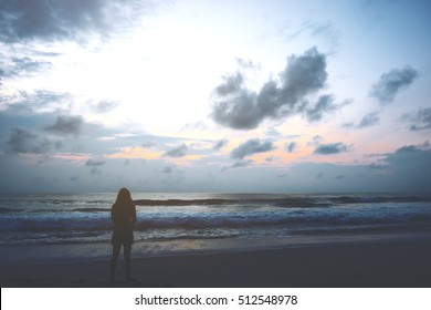 Silhouettes of a woman looking at view on the beach with sea and sunset background