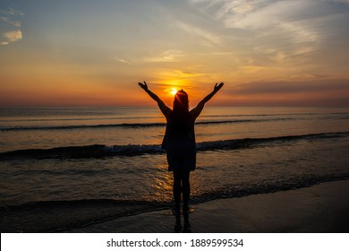 Silhouettes  of Woman raise hands up to the sunrise sky at the beach with copy space for your text, Christian concept of praise and worship.