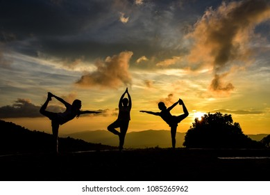 Silhouettes of woman with yoga posture practicing on the mountian at sunset.