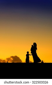 silhouettes of a women with her kid during sunset