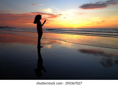 Silhouettes of a women praying during sunset.