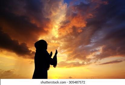 Silhouettes of a women praying during sunset. Image has grain or blurry or noise and soft focus when view at full resolution. (Shallow DOF, slight motion blur)
