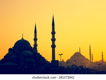Silhouettes of Yeni Cami Mosque and Suleymaniye Mosque at sunset, soft light effect. Panoramic view of muslim architecture landmarks with minarets, district of Sultanahmet in old Istanbul.