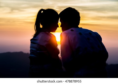Silhouettes of  Young Asian couple against the sunset sky.