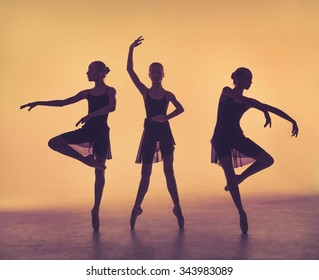 The silhouettes of young ballerinas posing on a gray background.