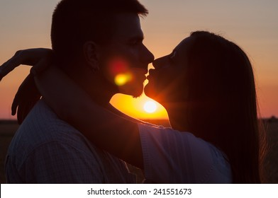 Silhouettes of young couple kissing at summer sunset.