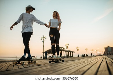Silhouettes of young couple riding longboards on the boardwalk outside
