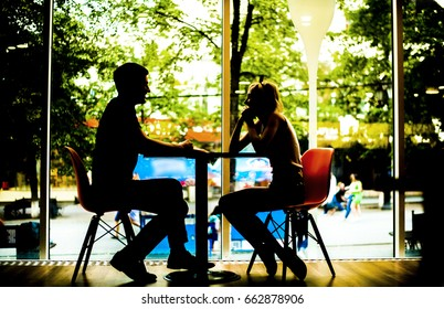 Silhouettes of young couple sitting at the tables in the restaurant or cafe. fast food restaurant. minimal interior with transparent windows. couple in the restaurant. man and woman, sitting at table