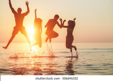 Silhouettes of young friends having fun in water for beach party - Group of happy people dancing and jumping inside sea on beautiful summer sunset - Joyful friends concept - Main focus on left girl
