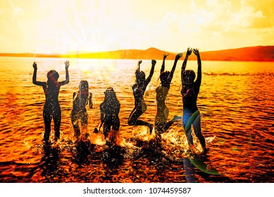 Silhouettes of young group of people jumping in ocean at sunset background. summer silhouettes of happy young people jumping in sea on the beach. vintage retro style with  sun flare
