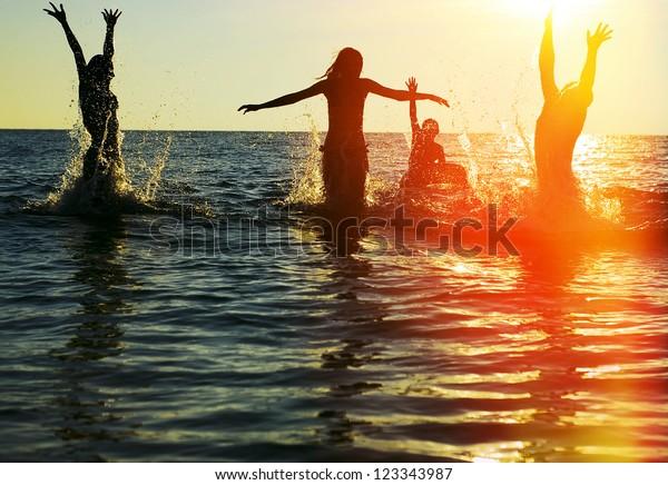 Silhuetas de jovens grupo de pessoas saltando no oceano ao pôr do sol