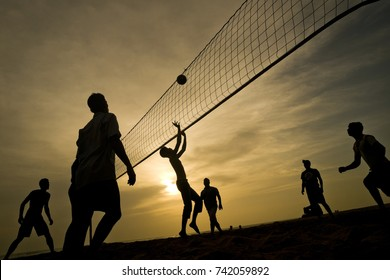 Silhouettes of young men playing volleyball on Varkala beach at sunset, Karnataka State, India