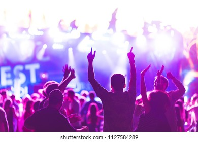 Silhouettes of young people during a bright performance, music festival. Delight from the performance and favorite music. Soft focus, shooting with high sensitivity in difficult conditions.