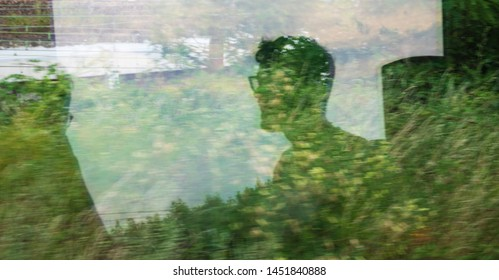 Silhouettes of young unrecognizable men passengers reflected in train window with green landscape passing by. Ecologic transport, environment sustainability, eco planet save earth creative concepts.