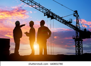 SilhouetteTeams Businessman engineer looking blueprint in a building site over Blurred construction site at sunset