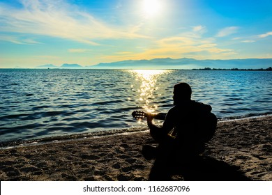 Silhouette.Young men playing guitar while sitting on the beach.