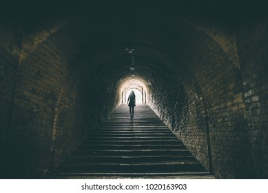 silhouettte of young woman in dark tunnel