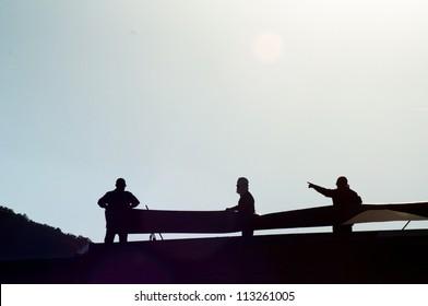 Silhoutte 3 men working on roof.