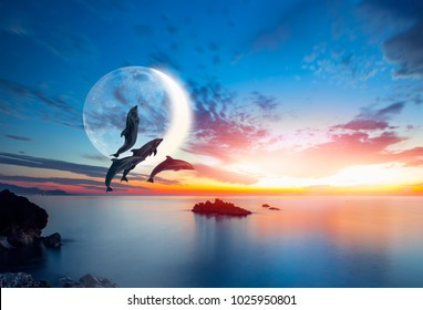 """Silhoutte of beautiful dolphins jumping up from the sea at sunset with crescent moon """"Elements of this image furnished by NASA """""""