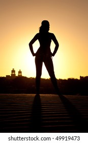 silhoutte of a beautiful woman in the sand at sunset