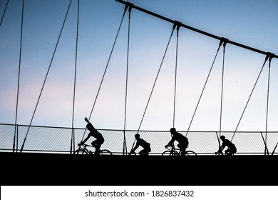 Silhoutte from bikers with a beautifull sunset.  Sports in kortrijk, groeningebrug.  Great composition of bikers in harmony, recreation in belgium.  four bikers in the evening with one waving.