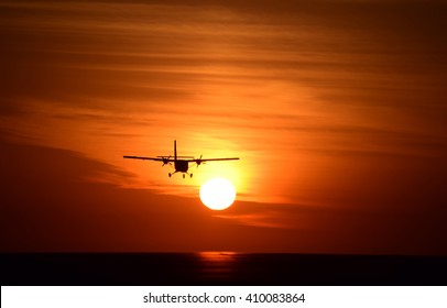 silhoutte of a civilian aircraft or a small twin engine aeroplane taking off from the runway in a evening  sunset time with yellow orange sun and bright yellow sky in the background.